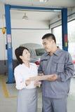 Mécanicien gai Explaining au client et représentation de garage lui du Bill Image stock