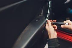 Mécanicien installant le moteur central de serrure de porte de voiture image stock