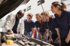 Mécanicien instruisant des stagiaires autour d'un moteur de voiture, angle faible images libres de droits