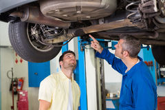 Mécanicien montrant à client le problème avec la voiture Photographie stock