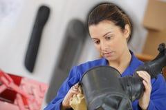 Mécanicien polissant l'objet industriel dans le garage Images libres de droits