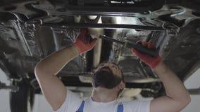 Mécanicien professionnel barbu inspectant avec la lampe à la station service de réparation Homme habile dans la voiture de répara banque de vidéos