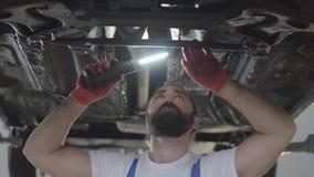 Mécanicien professionnel barbu inspectant avec la lampe à la station service de réparation Homme habile dans la voiture de répara clips vidéos