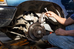 Mécanicien réparant le disque de frein et petit groupe de la roue images stock