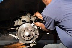 Mécanicien réparant le disque de frein et petit groupe de la roue Images libres de droits