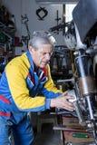 Mécanicien réparant un moteur de motocyclette Photo stock