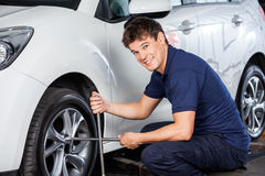 Mécanicien Repairing Car Tire avec Rim Wrench photo stock
