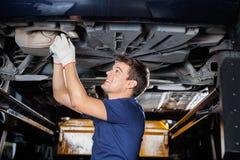 Mécanicien Repairing Underneath Car avec la clé Image stock