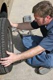 Mécanicien retirant le pneu Images libres de droits