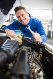 Mécanicien souriant au moteur de fixation d'appareil-photo Image stock