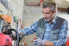Mécanicien travaillant à l'équipement de jardinage Photographie stock