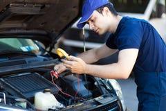 Mécanicien travaillant à un moteur de voiture photographie stock libre de droits