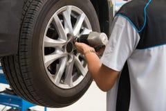 Mécanicien travaillant à une roue de voiture serrant ou détachant le boulon Photos libres de droits