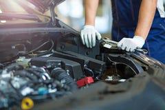 Mécanicien travaillant au moteur de voiture dans l'atelier de réparations automatiques photographie stock libre de droits