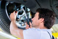 Mécanicien travaillant dans l'atelier de voiture Photographie stock libre de droits