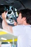 Mécanicien travaillant dans l'atelier de voiture sur la roue Image libre de droits