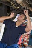 Mécanicien travaillant sous le véhicule Images libres de droits