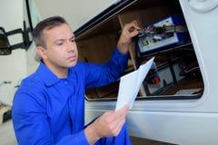 Mécanicien vérifiant des électricités sur campervan photo libre de droits