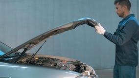 Mécanicien vérifiant le niveau d'huile dans un atelier de voiture Homme dans le moteur de service de camion Photo libre de droits