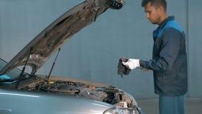 Mécanicien vérifiant le niveau d'huile dans un atelier de voiture Homme dans le moteur de service de camion Images stock