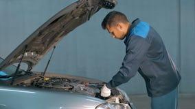 Mécanicien vérifiant le niveau d'huile dans un atelier de voiture Homme dans le moteur de service de camion Photos libres de droits
