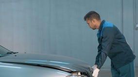 Mécanicien vérifiant le niveau d'huile dans un atelier de voiture Homme dans le moteur de service de camion Photos stock