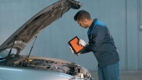Mécanicien vérifiant le niveau d'huile dans un atelier de voiture Homme dans le moteur de service de camion Photo stock