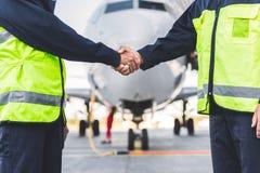 Mécanique joignant des mains à l'aéroport Photographie stock