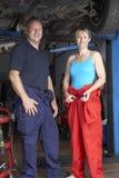 Mécanique mâle et féminine travaillant au véhicule Image stock