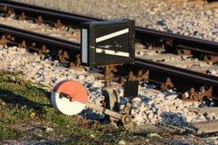Mécanisme ferroviaire partiellement rouillé fort de commutateur en métal rouge et blanc monté sur le conseil en bois à côté des v image stock