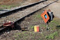 Mécanisme ferroviaire rouillé de commutateur avec le signe partiellement rouillé en métal à côté des voies de chemin de fer aband photos libres de droits