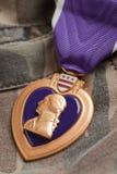 Médaille de guerre de coeur pourpré sur le matériau de camouflage Images stock