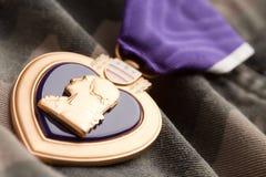 Médaille de guerre de coeur pourpré sur le matériau de camouflage image stock