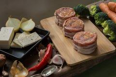 Médaillons crus de filet de porc remplis de saucisse de chorizo et enveloppés avec le lard Photos libres de droits