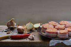Médaillons crus de filet de porc remplis de saucisse de chorizo et enveloppés avec le lard Images libres de droits