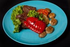 Médaillons de veau avec les légumes grillés sur un fond noir, vue supérieure image stock