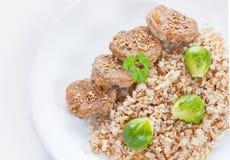 Médaillons et riz brun avec des choux de bruxelles sur le blanc Images libres de droits