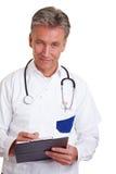 Médecin aîné avec la planchette Photos stock