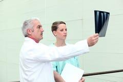 Médecin aîné et infirmière observant un rayon X Photos libres de droits