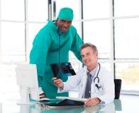 Médecin aîné et jeune chirurgien étudiant un rayon X Photos stock