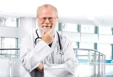 Médecin aîné songeur dans la clinique Image libre de droits