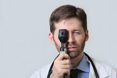 Médecin avec la barbe utilisant l'ophthalmoscope Photo stock