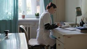 Médecin dans le bureau à la table docteur dans un hôpital très vieil dans le bureau Image stock