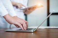 Médecin dans le résultat d'écriture et la prescription uniformes blancs dans l'ordinateur portable d'ordinateur, concept médical photographie stock