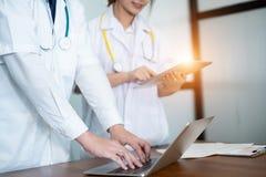Médecin dans le résultat d'écriture et la prescription uniformes blancs dans l'ordinateur portable d'ordinateur, concept médical photographie stock libre de droits