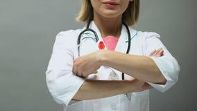 Médecin de femme avec le ruban rouge posant pour la caméra, conscience de SIDA, la maladie de sti banque de vidéos
