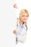Médecin de sourire de jeunes posant sur un panneau blanc images libres de droits