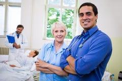 Médecin et infirmière de sourire se tenant avec des bras croisés Photos stock