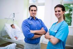 Médecin et infirmière de sourire se tenant avec des bras croisés Images stock