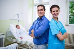 Médecin et infirmière de sourire se tenant avec des bras croisés Photographie stock libre de droits